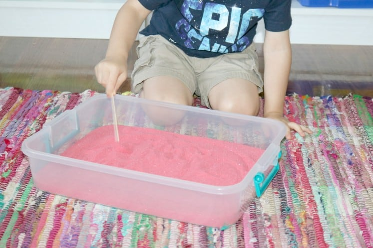preschooler writing in sand with craft stick