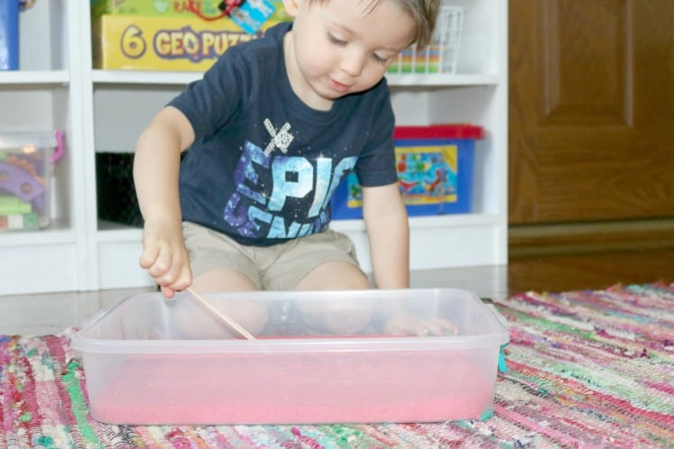 preschooler writing letters in sand with craft stick
