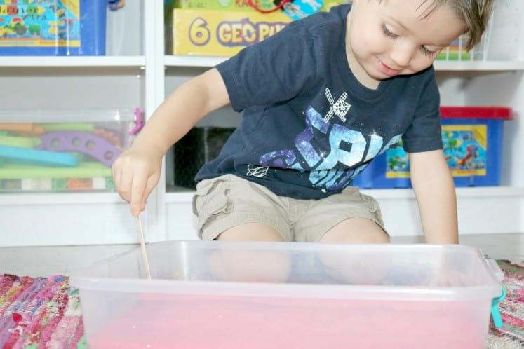 preschooler making letters in colored sand with craft stick