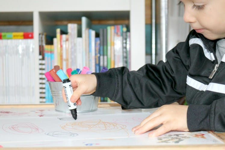 preschooler coloring on a white piece of cardstock