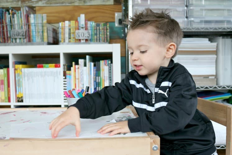 preschooler picking up piece of white cardstock on table