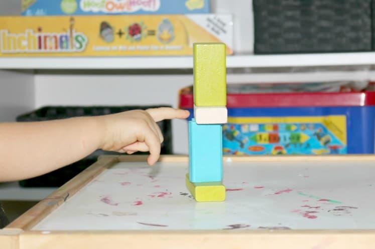 preschooler pointing to tower of wooden blocks