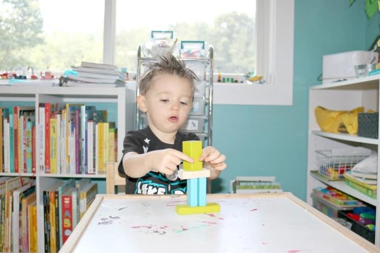 preschooler building a tower of blocks