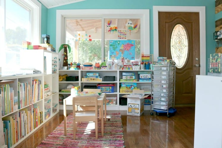 preschool space with bookshelves, rolling cart and table and chairs