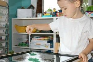 preschool using eye dropper to put watercolor onto mirror