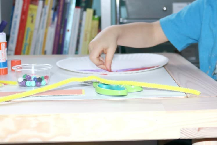 preschooler gluing rainbow collage pieces to paper plate