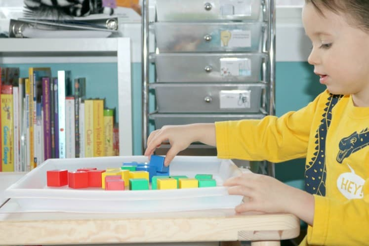preschooler stacking block manipulatives on tray