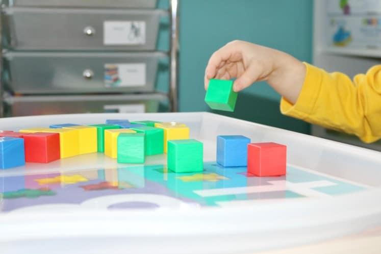 preschooler picking up manipulative block