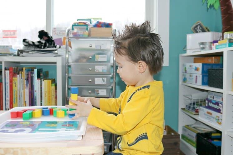 preschooler stacking manipulative blocks
