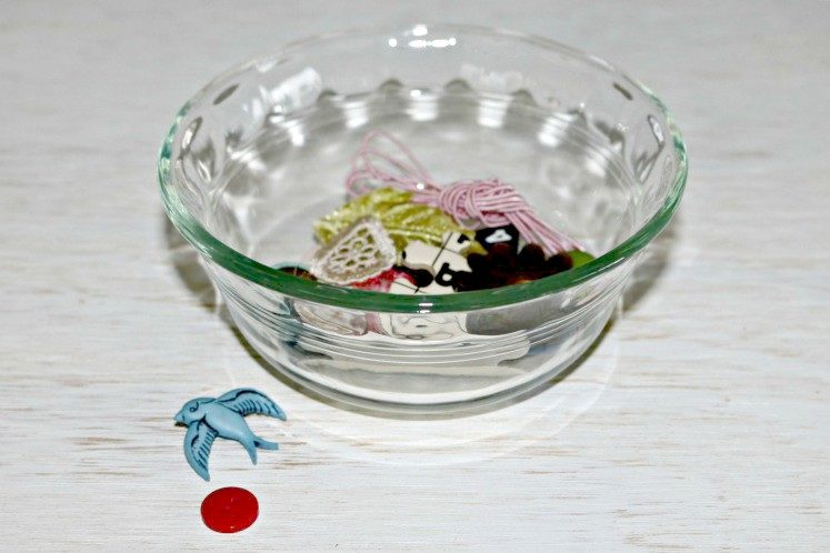 a few buttons on desk next to clear dish containing small embellishments