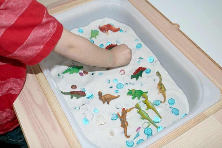 preschooler playing pretend with dinosaur figurines in sensory bin