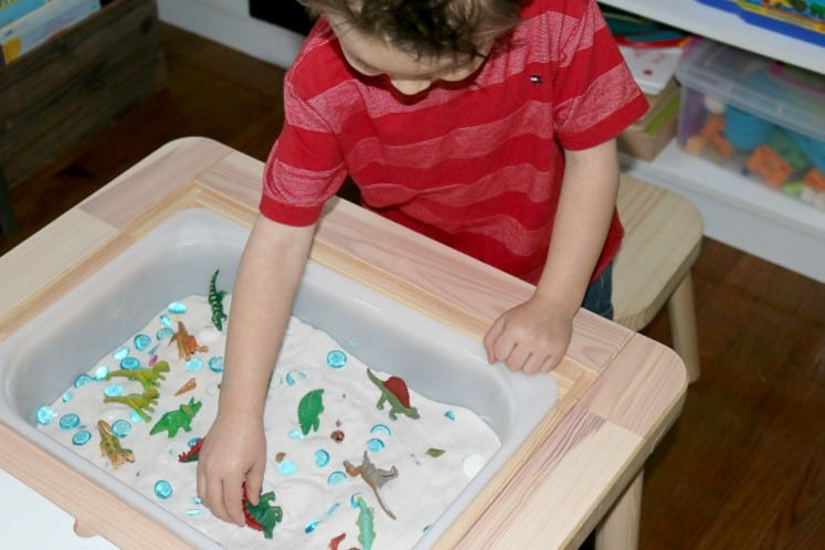 preschooler playing with dinosaur toys in sand sensory bin