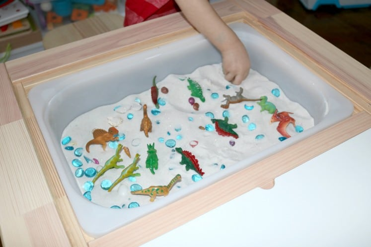 preschooler picking up small stone from dinosaur sensory bin