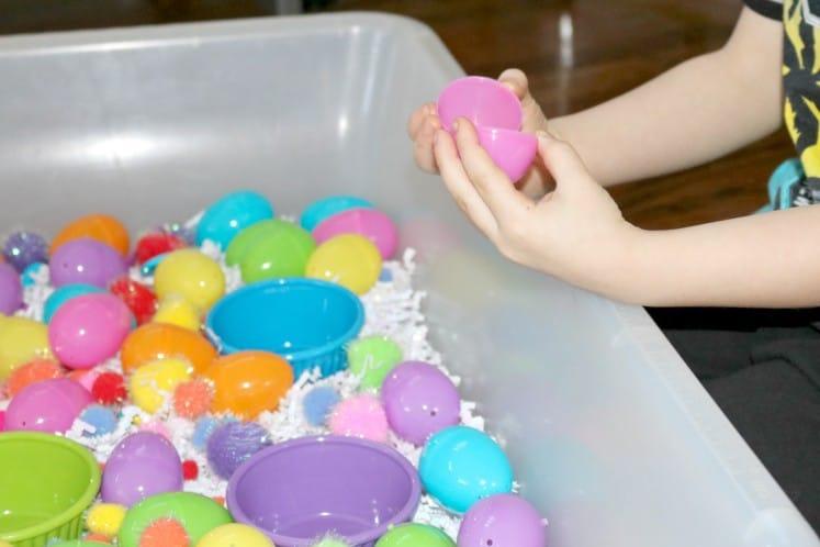 preschooler looking inside plastic Easter egg