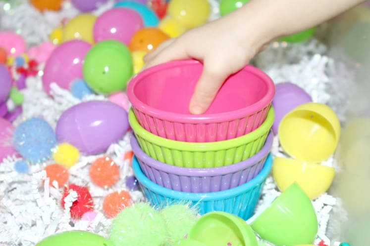 preschoolers stacking colorful plastic bowls in Easter sensory bin