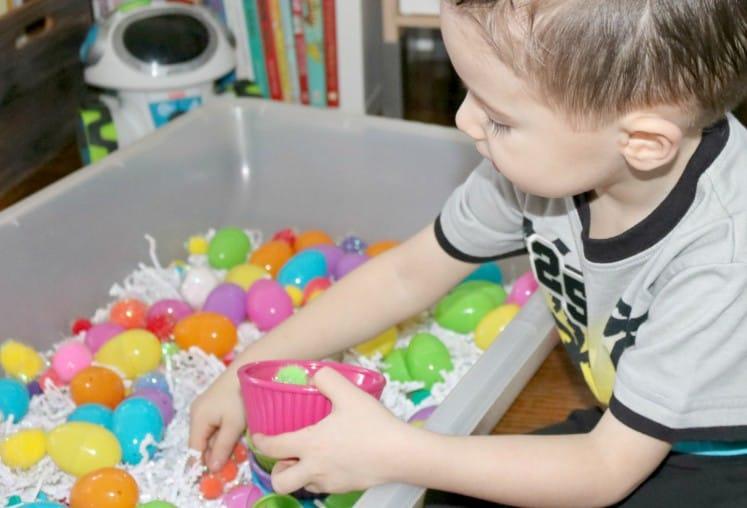 preschooler filling plastic bowl with pompoms