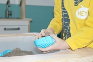 preschooler filling dinosaur bone sand mold with sand