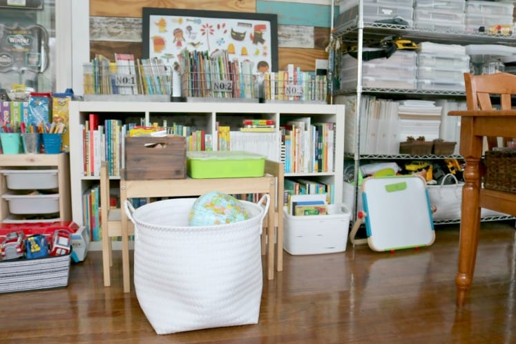 child's play area with book shelves, table and chairs, and baskets full of toys