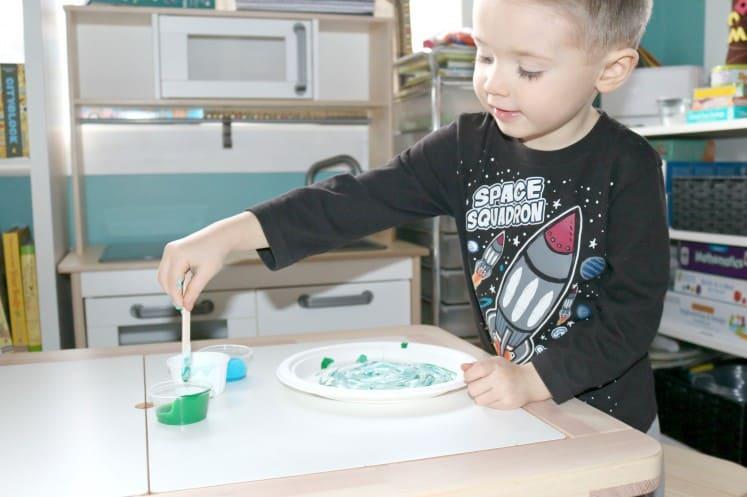 preschooler mixing green paint with craft stick