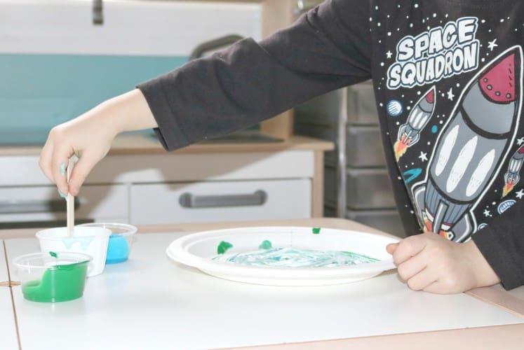 preschooler stirring paint with craft stick