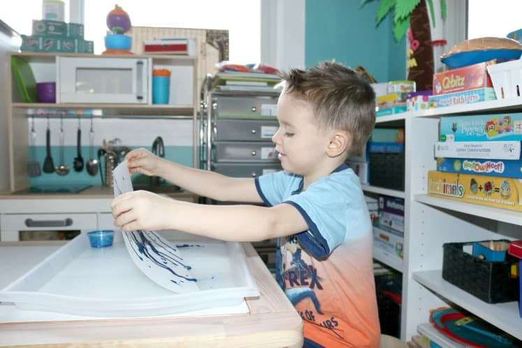 preschooler holding cardstock process art upright so paint drips down paper and makes waterfall effect