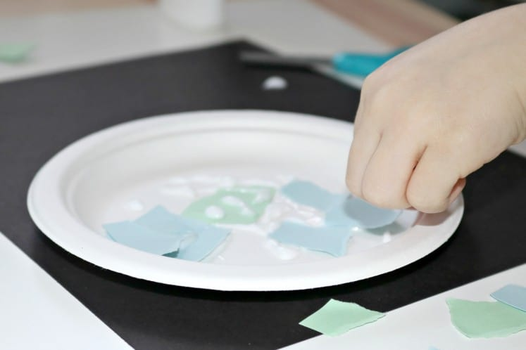 preschool gluing small pieces of cardstock onto paper plate