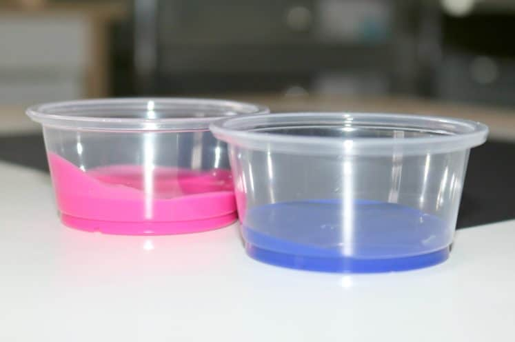 pink and blue paint in clear cups