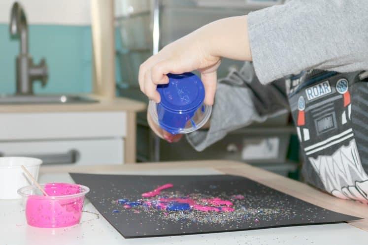 preschooler pouring blue paint onto galaxy glitter process art
