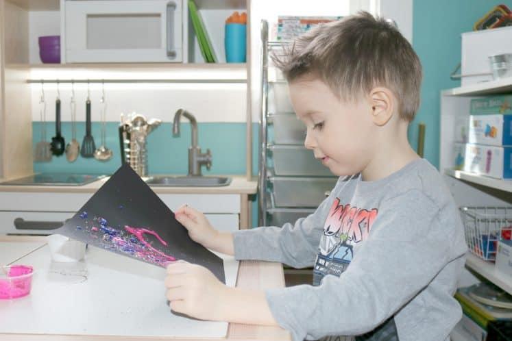 preschooler holding up galaxy glitter process art