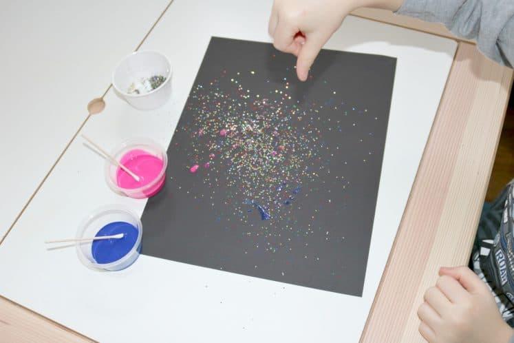 preschooler sprinkling glitter on galaxy glitter process art