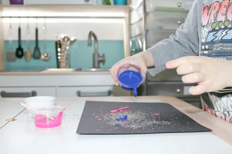 preschooler pouring paint onto black cardstock
