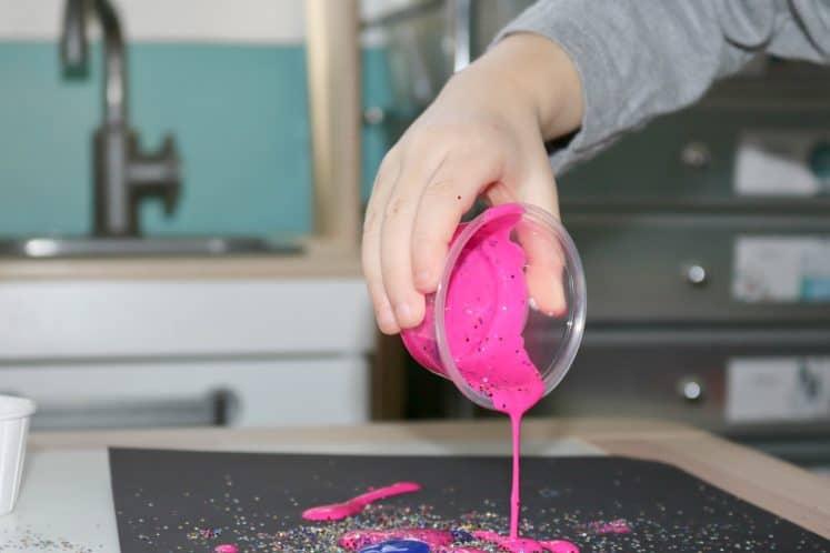 preschooler pouring pink paint onto black cardstock