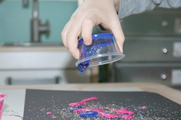 preschooler pouring paint and glitter mixture onto black cardstock