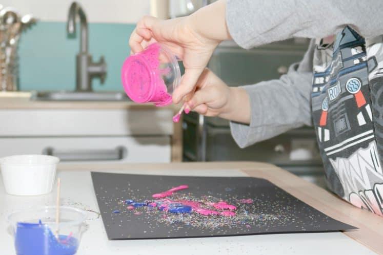 preschooler pouring pink paint onto galaxy glitter process art