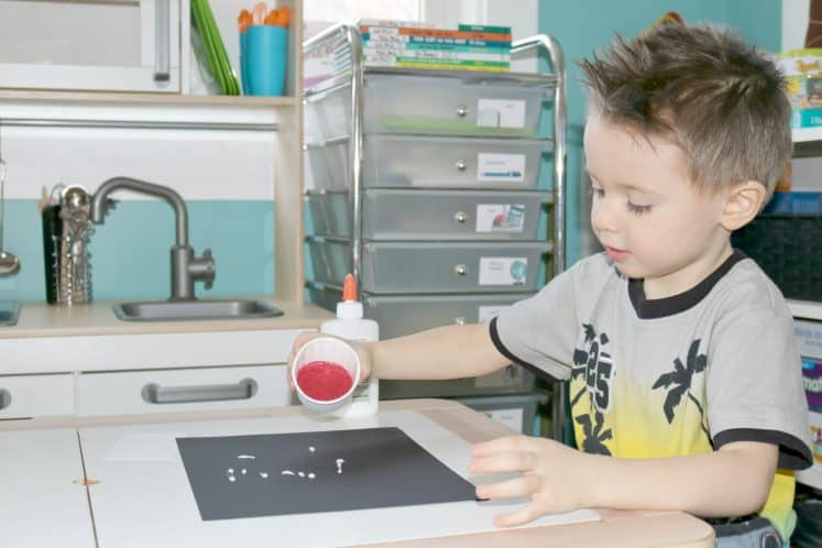 preschooler pouring sand from paper cup onto black cardstock to make Mars process art