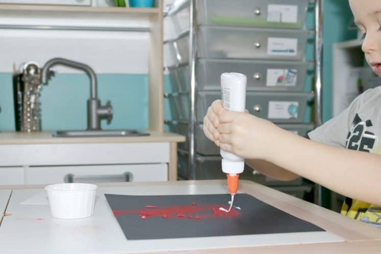 preschooler squeezing glue onto black cardstock containing red sand