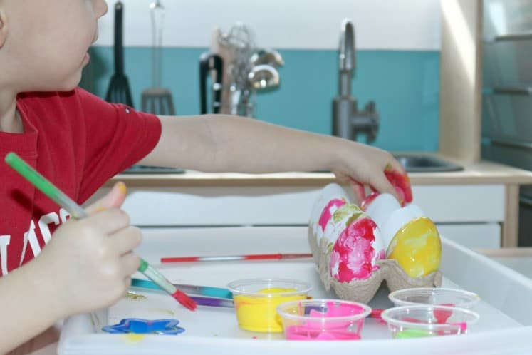 preschooler reaching for artificial egg to paint