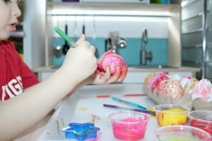 preschooler painting artificial egg
