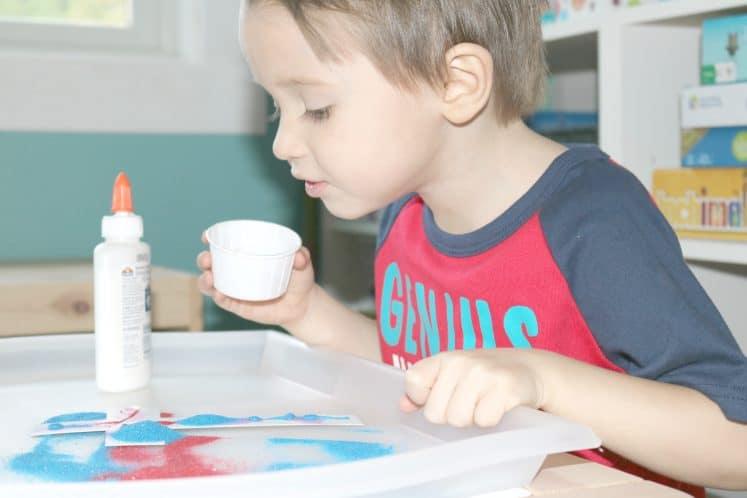 preschooler looking at sand cross paper craft