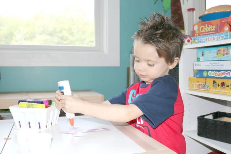 preschooler squeezing glue onto cross paper craft