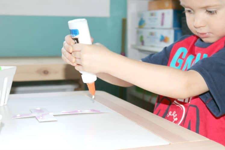 preschooler putting glue on cross craft