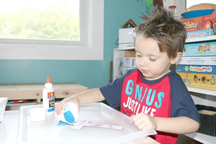 preschooler pouring blue sand onto paper cross