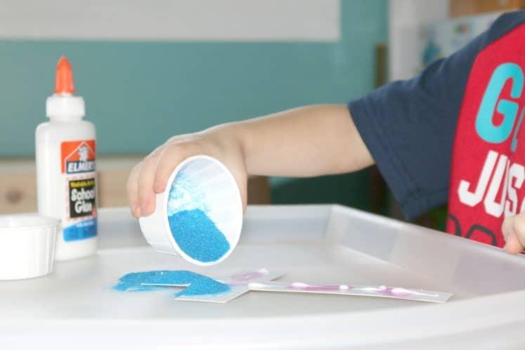 preschooler pouring blue sand on paper cross