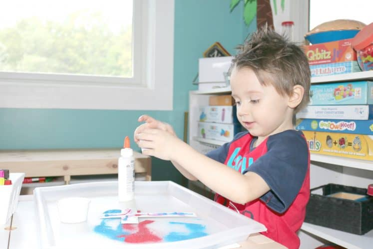 preschooler holding cup filled with sand