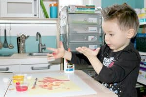 preschooler with paint all over his hands making planet art