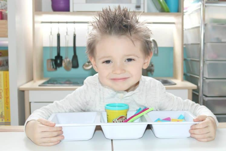 preschooler sitting at table with a tray of art supplies