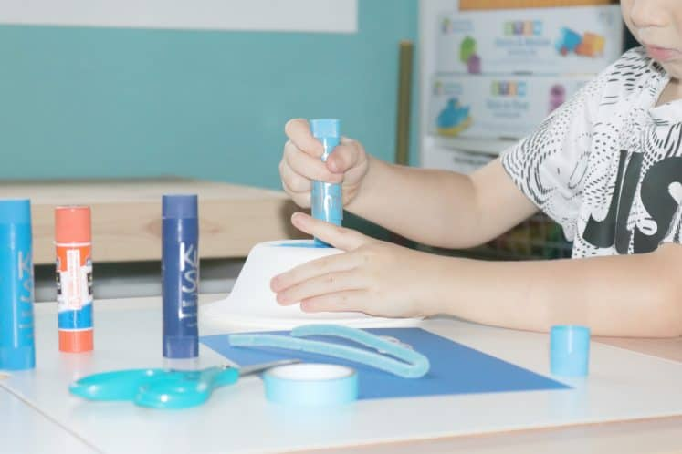 preschooler painting paper bowl to make whale craft