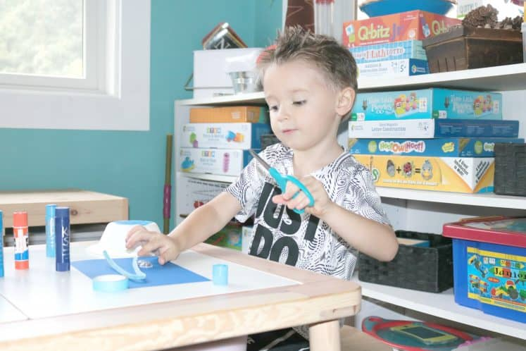 preschooler cutting cardstock to make whale craft