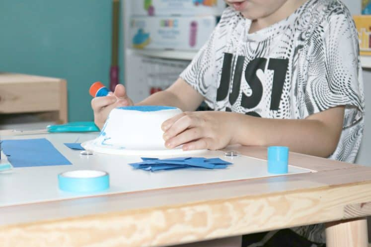 preschooler gluing cardstock to paper bowl to make whale craft
