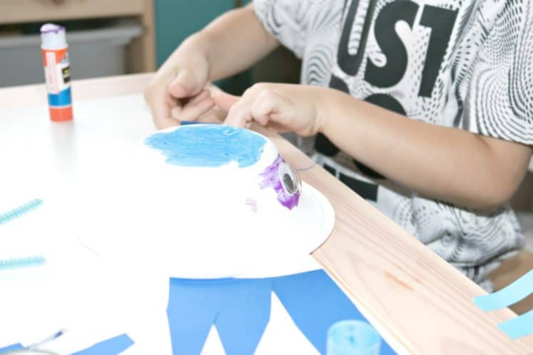 preschooler using paper bowl and cardstock to make whale craft